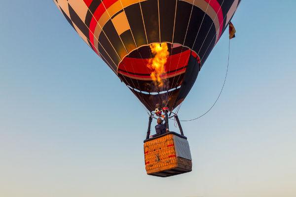 O ar no interior do balão recebe energia térmica da chama.