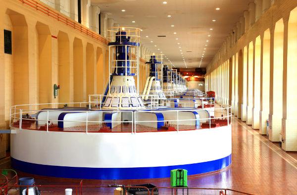 As turbinas das hidrelétricas são como grandes bobinas que giram, produzindo corrente elétrica.