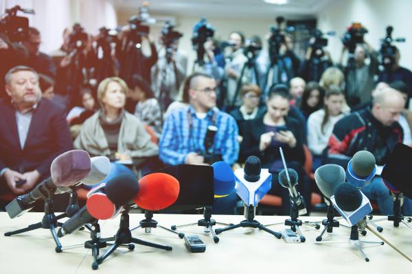 Jornalistas reunidos em uma coletiva de imprensa.