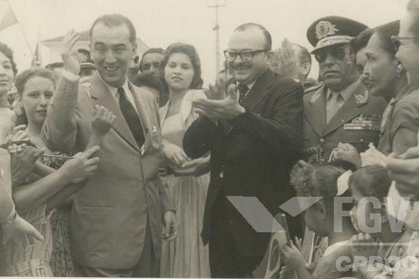 Juscelino Kubitschek (de terno claro, acenando) não economizou gastos na construção de Brasília.[1]