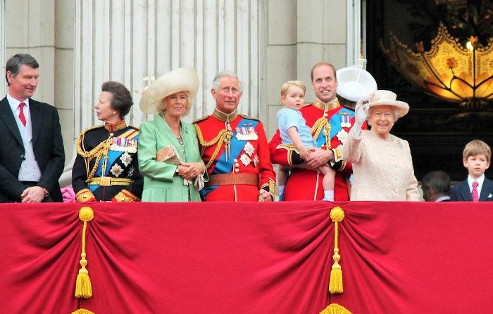Na imagem estão Charles, William (ambos de vermelho), George (no colo de William) – herdeiros do trono – e a rainha Elizabeth. [3]
