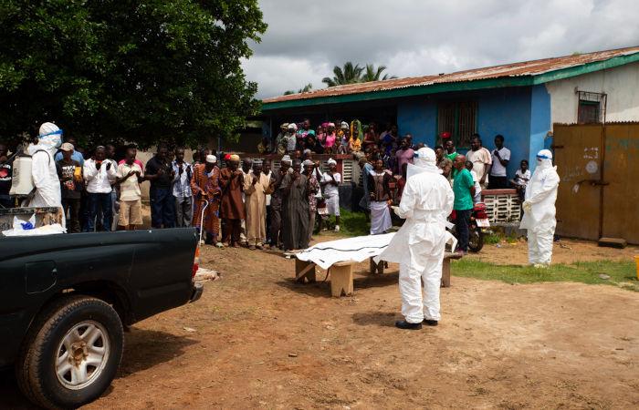 Profissionais que realizarão o enterro do corpo e conhecidos de uma vítima do ebola prestando a última homenagem. [1]