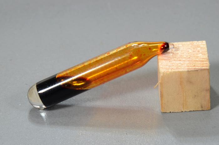 Vidraria contendo amostra de bromo líquido apoiada sobre um bloco de madeira.