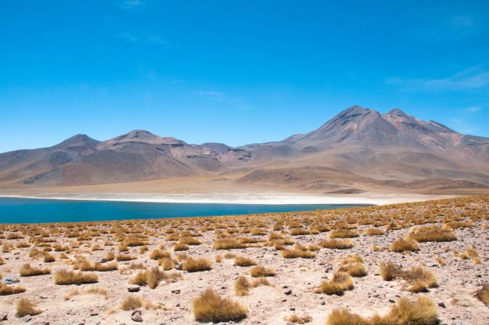 Foto do deserto do Atacama; ao fundo, uma lagoa e montanhas.