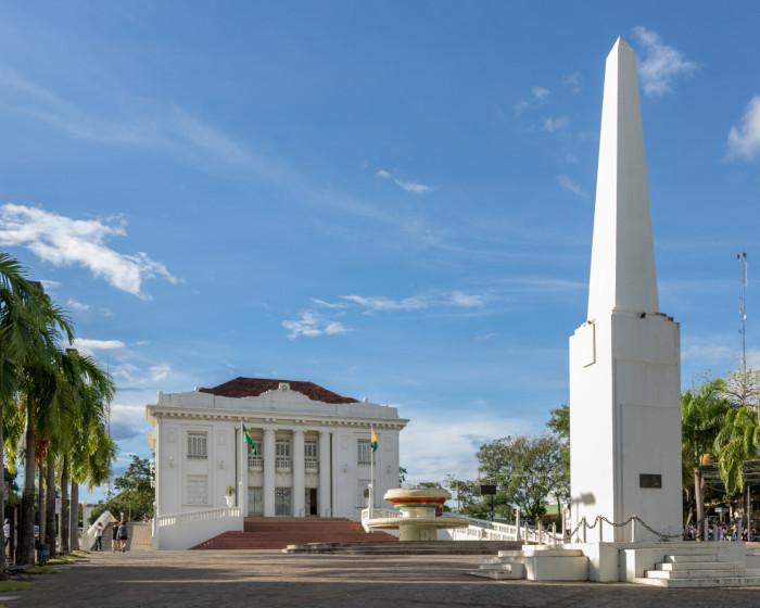 Foto do Palácio Rio Branco, um prédio, com um chafariz à sua frente, rodeado de coqueiros em uma praça.