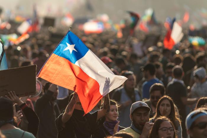 Foto de pessoas em um protesto; no centro e em destaque, a bandeira do Chile.
