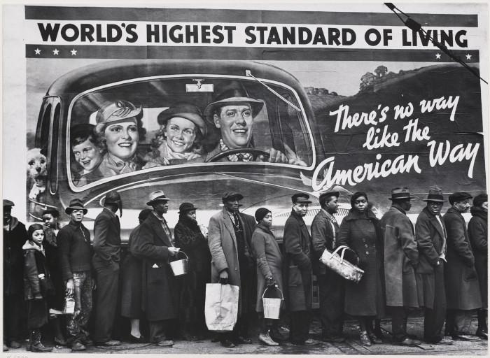"""Cidadãos em frente de um cartaz que pregava o """"american way of life""""."""