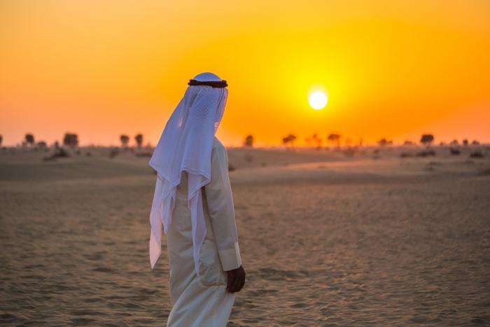Homem vestindo trajes típicos muçulmanos caminhando em um deserto.