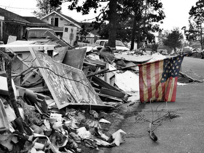 Foto em preto e branco de destroços de Nova Orleans e a bandeira dos Estados Unidos colorida.