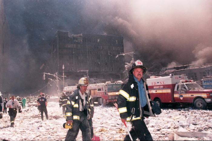 Foto de bombeiros trabalhando nos destroços dos ataques às Torres Gêmeas.