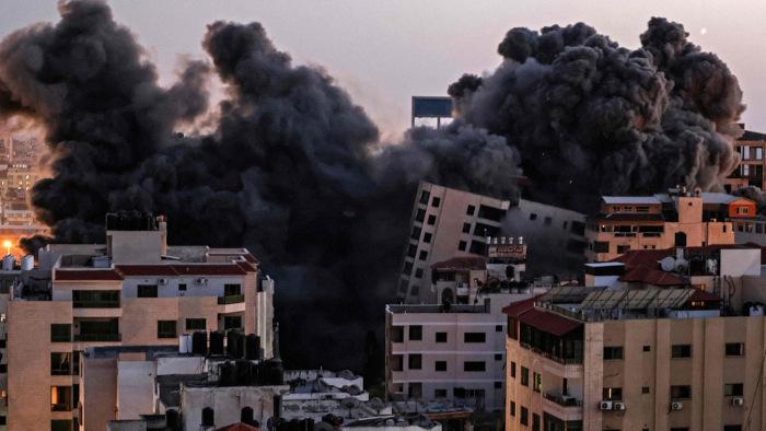 Foto após ataque na Faixa de Gaza com fumaça preta entre destroços.