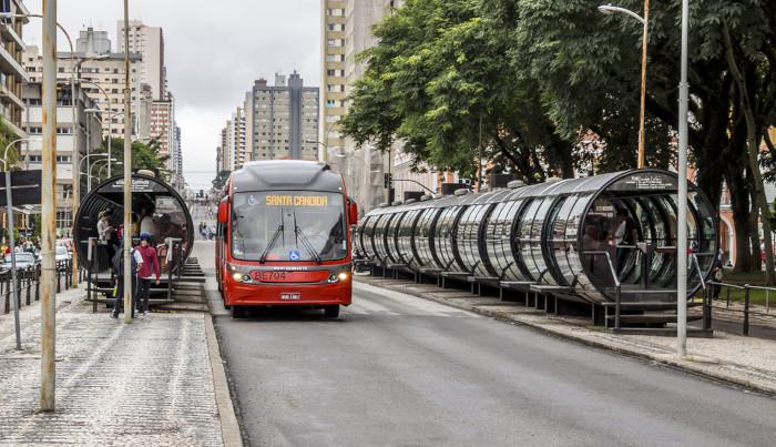 Foto de passageiros embarcando em ônibus.