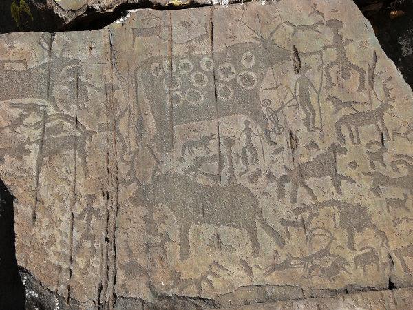 Pessoas e animais representados em um petróglifo, representação típica do Mesolítico. Montanhas Altai na Sibéria, Rússia.