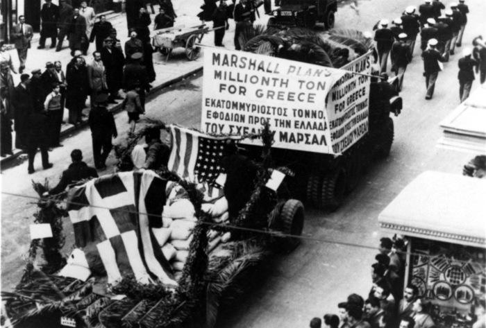 """Foto de desfile militar com tanques e faixa escrita em inglês e grego: """"Plano Marshall: Milhões de toneladas para Grécia""""."""