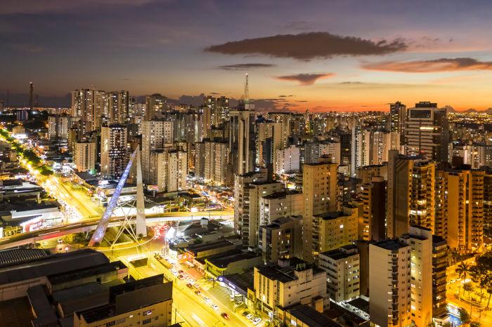Vista aérea da cidade de Goiânia, sendo possível visualizar monumento em viaduto no Setor Bueno e vários prédios ao redor.