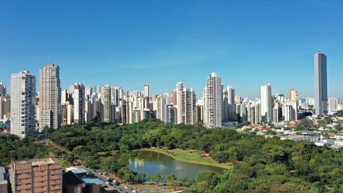 Vista panorâmica de um parque em Goiânia, cercado por muitos edifícios modernos e árvores.
