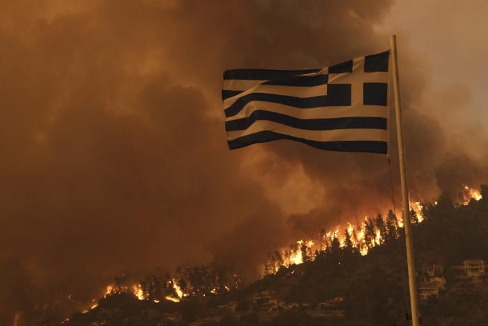 Bandeira da Grécia em ambiente pegando fogo.