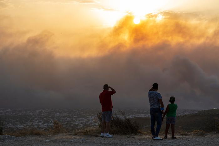 Pessoas observando ambiente devastado por um incêndio.