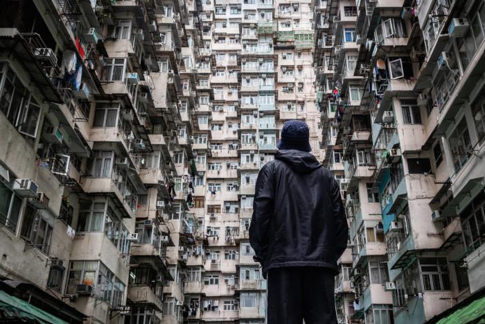Homem observando prédios habitacionais.