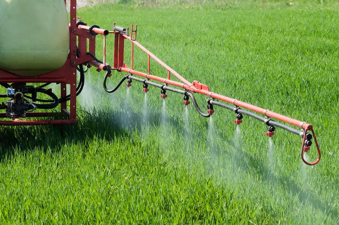 Máquina fazendo a aplicação de agrotóxico no campo.