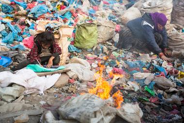 Criança com os pais em um lixão em Katmandu, Nepal