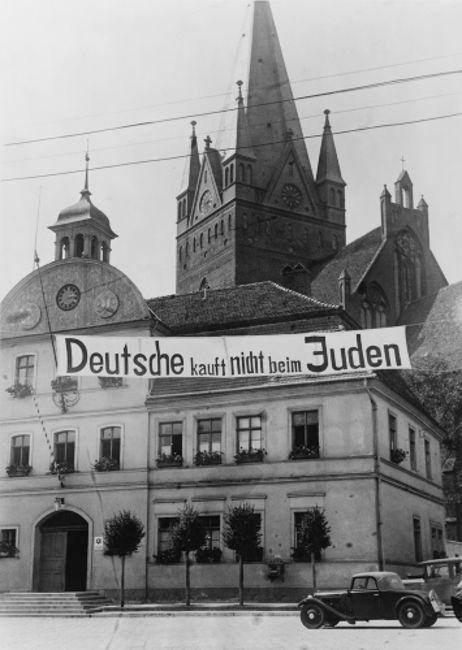 """Na Alemanha nazista, eram comuns placas e faixas como essa contra judeus. Na imagem, está escrito: """"Alemães não compram em lojas de judeus"""".*"""