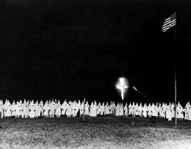 Reunião dos membros da Ku Klux Klan. O capuz e a cruz em chamas são característicos