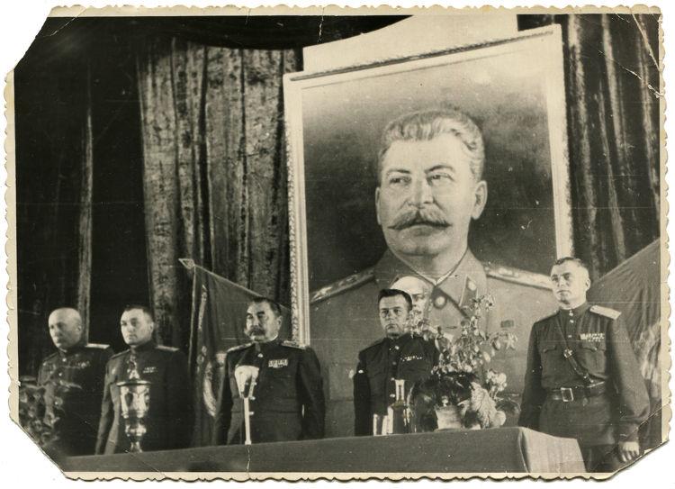 No Stalinismo, existia um forte culto à personalidade de Stalin. Na imagem, temos um encontro do governo soviético com uma imagem de Josef Stalin ao fundo.**