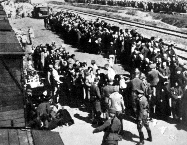 Judeus enfileirados para embarcar no vagão que os transportaria para Auschwitz.