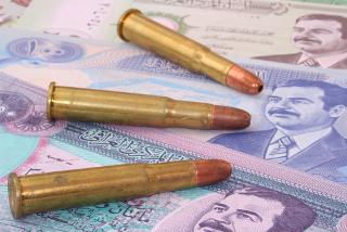 Imagem de balas e dinares iraquianos com a figura de Saddam Hussein