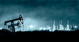 """Na imagem vemos """"cavalos de pau"""" extraindo petróleo e uma refinaria ao fundo de onde se obtêm os seus derivados, que são frações de hidrocarbonetos"""