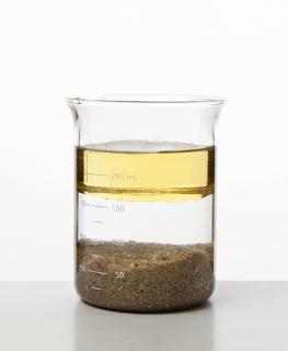 A água está sendo usada para separar a mistura de óleo e areia