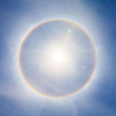 Ao se chocar com cristais de gelo, a luz solar é refratada e forma um anel luminoso ao redor do Sol