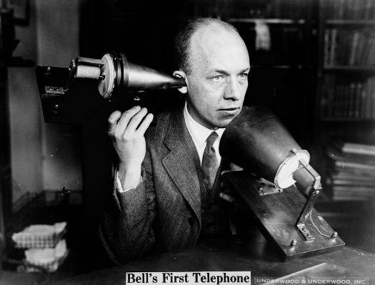 Acima, homem usando o primeiro protótipo de telefone criado por Graham Bell *