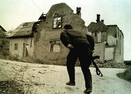 Soldado correndo em meio a ruínas durante um tiroteio entre tropas bosníacas e sérvio-bósnios em 1993 *