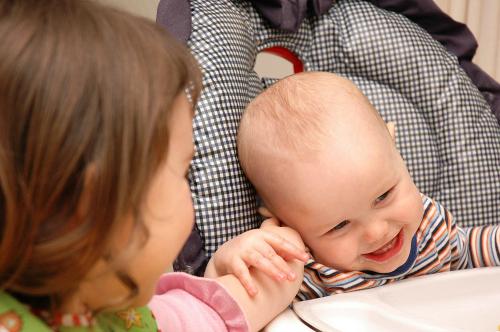 Criança fazendo cócegas em outra.