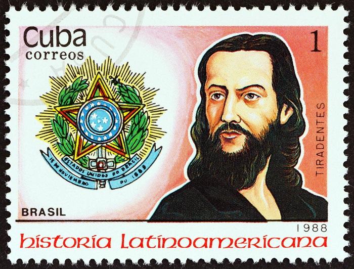 Imagem de um selo cubano que apresenta a imagem mitificada de Tiradentes, com cabelos e barba longos*
