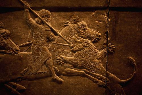 Retrato feito em pedra do rei assírio Assurbanipal caçando um leão*