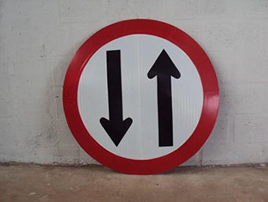Placa de trânsito representando duplo sentido na via, através do uso de dois vetores